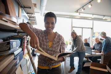 Portrait of mature woman holding book in creative studio