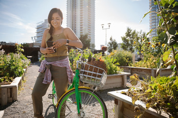 Young woman with smart phone and bicycle in sunny, urban community garden