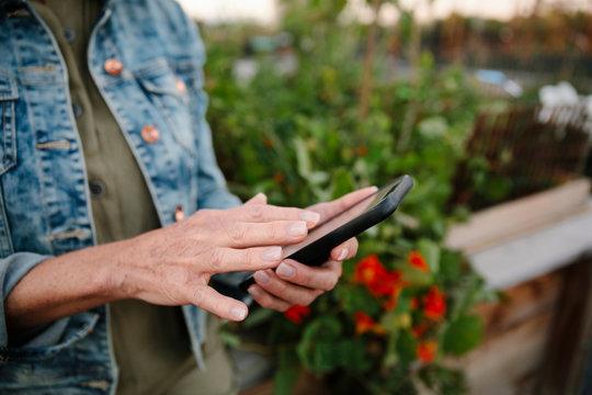 Close up mature woman using smart phone in garden