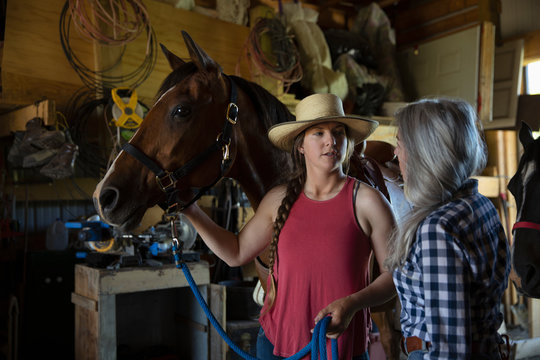 Mother and daughter talking with horse in stable