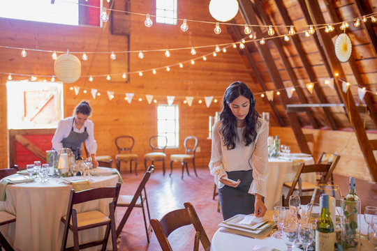 Female wedding planner setting placecards on table for wedding reception