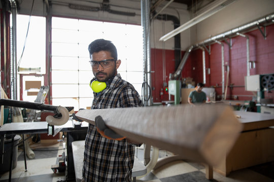 Man wearing protective workwear holding wood in maker space