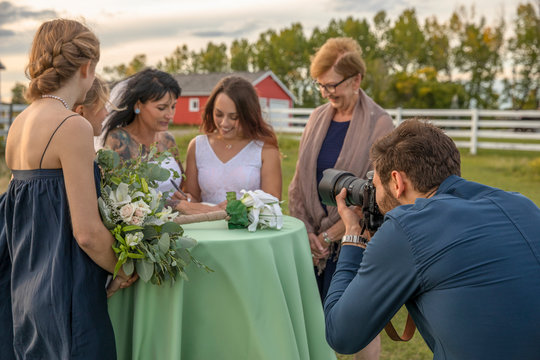 Photographer capturing lesbian brides signing marriage certificate in rural field
