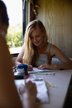 Young woman planning trip with notebook in motorhome