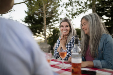 Mature women sitting with wine outside on ranch