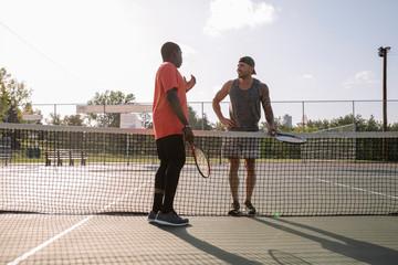 Two men talking over tennis net Fototapete