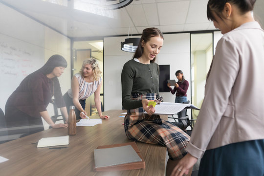 Young woman reading document in modern office with female colleagues