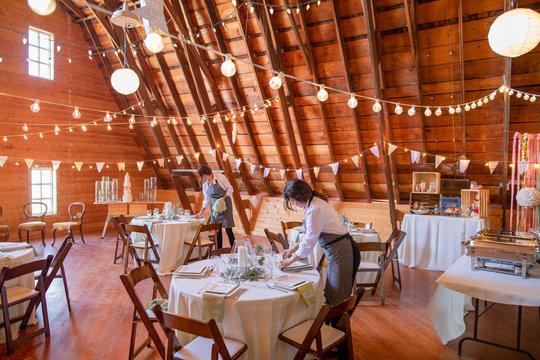 Female servers preparing tables for wedding reception in barn