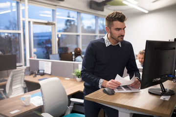 Young man using computer at standing desk in office