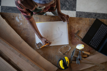 Overhead view of woman designing furniture on work bench