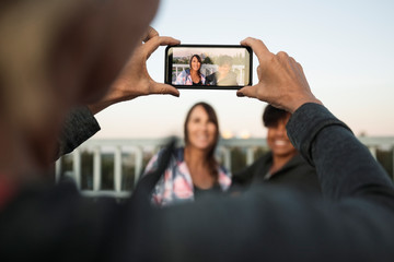 Person photographing two women on smart phone
