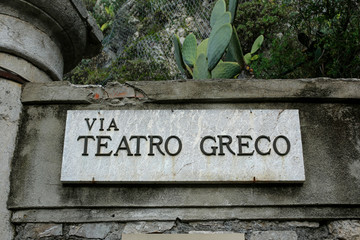 signpost with Via Teatro Greco text next to the entrance to Ancient theatre of Taormina, Sicily, Taormina