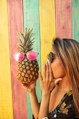 Playful young woman talking to pineapple with sunglasses on summer patio
