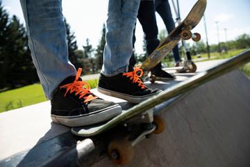 Close up teenage boy's foot on skateboard on ramp in skate park