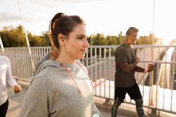 Woman in sweatshirt walking over footbridge with running friends