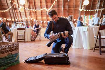 Male photographer preparing camera equipment at wedding reception
