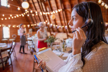 Female wedding planner with clipboard and headset preparing for wedding reception