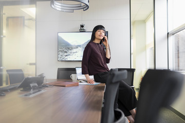 Chinese businesswoman talking on smart phone in boardroom and smiling