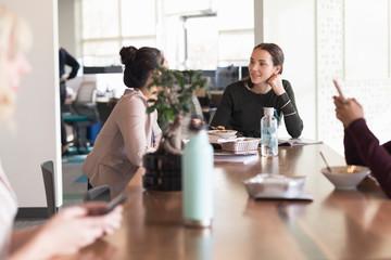 Young women enjoying working lunch in modern office Fotobehang