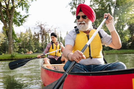 Mature Indian man canoeing with son