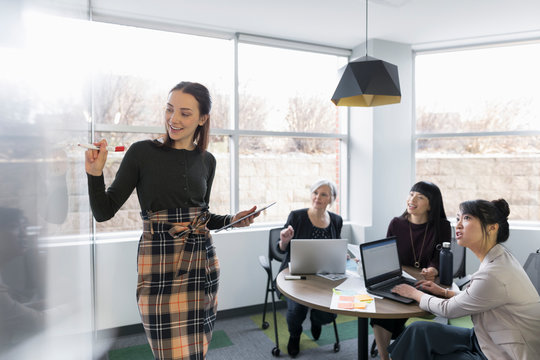 Young woman at whiteboard presenting to female colleagues