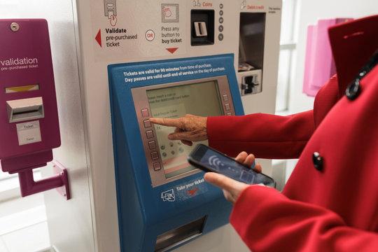 Senior woman buying train ticket from machine in railway station