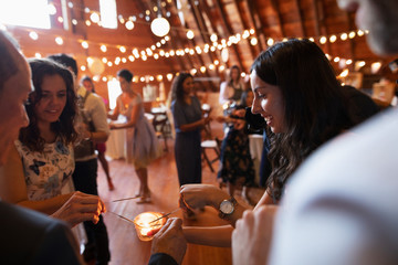Wedding guests lighting sparklers with candle at wedding reception