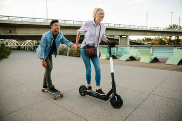 Playful young couple riding scooter and skateboard on urban sidewalk