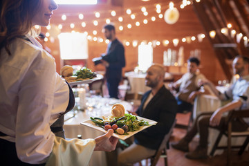 Female server carrying plates of Food at wedding reception