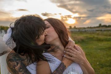 Affectionate lesbian brides kissing