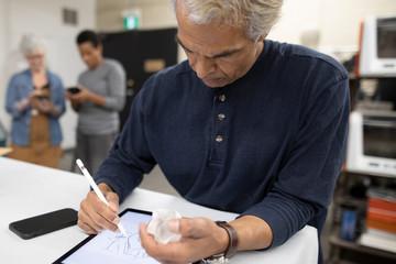 Mature man using digital tablet in 3d printing studio