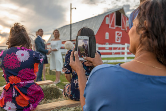 Female wedding guest with camera phone photographing couple getting married in rural field