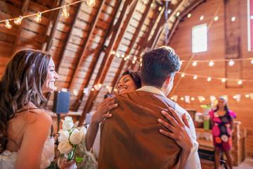 Happy wedding guest hugging bride and groom at wedding reception