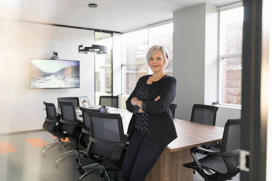 Portrait of mature businesswoman in modern office with arms folded