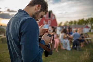 Male photographer working outdoor, rural wedding reception