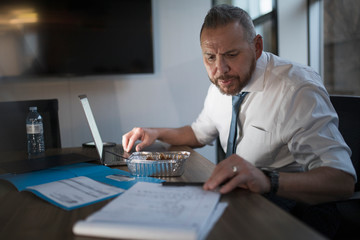 Mature man working overtime with take out Food in office