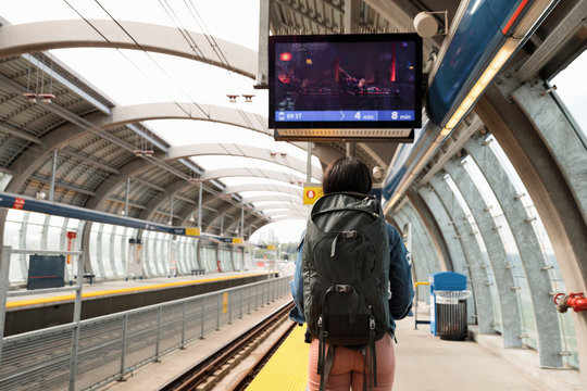 Rear view of young woman with backpack on railway station platform