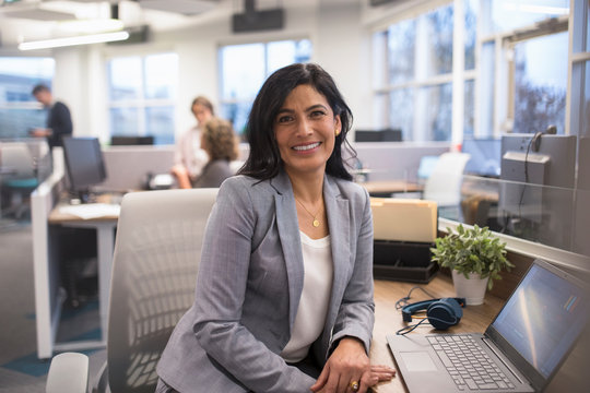 Portrait of mature businesswoman sitting at desk smiling