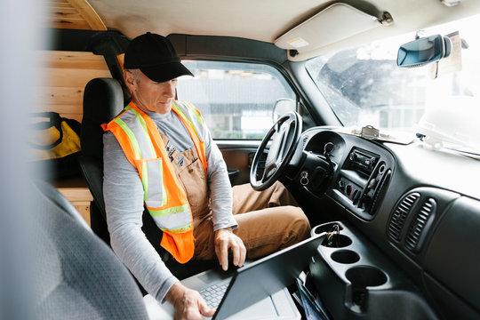 Construction worker using laptop in van