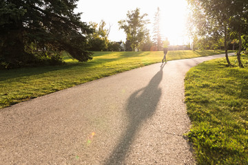 Man running on path in park in bright sunlight