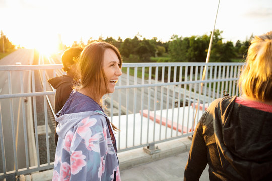 Cheerful mature women walking on footbridge in sunlight