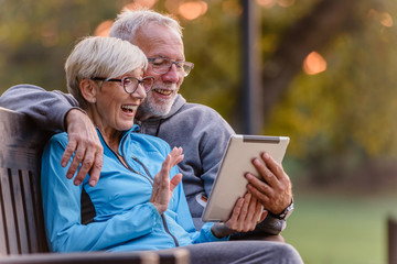 Smiling senior active couple sitting on the bench looking at tablet computer. Using modern...
