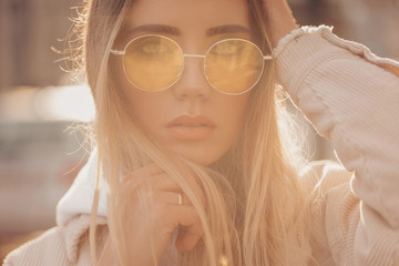 Beautiful stylish blonde woman in yellow sunglasses in outdoor.