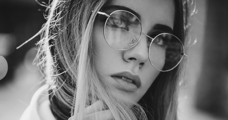 Portrait of beautiful stylish blonde woman in clear sunglasses in outdoor.