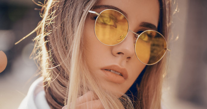 Portrait of beautiful stylish blonde woman in yellow sunglasses in outdoor.