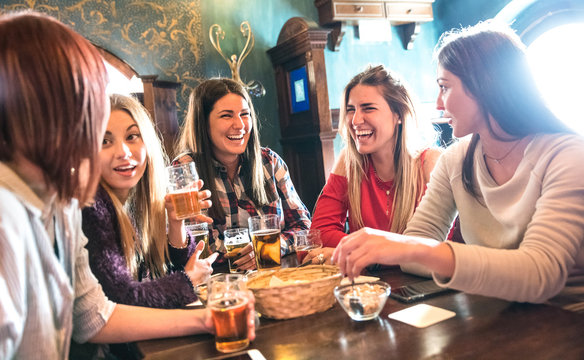 Happy women drinking beer at brewery restaurant - Female friendship concept with young girlfriends enjoying time together and having genuine fun at cool vintage pub - High iso image with soft focus