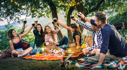 Happy friends having fun at vineyard on sunset - Young people millenial toasting at open air picnic under string light - Youth friendship concept with guys and girls drinking red wine at bar-b-q party