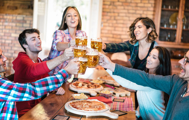 Friends group drinking beer and eating pizza at bar restaurant - Friendship concept with young people having fun together at risto pub pizzeria on happy hour - Focus on pint glasses - Warm filter