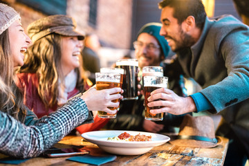 Friendly guys approaching happy girls at brewery pub outdoor on winter time - Friendship concept with young people having drunk fun together drinking beer at happy hour promotion - Vivid color filter