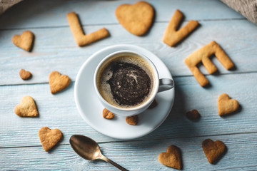 Cup of coffee and a message from a sweet cookie in the form of the word love. Romantic Valentine's...
